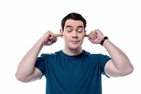 pic of middle finger  - Middle aged man plugging ears with fingers - JPG