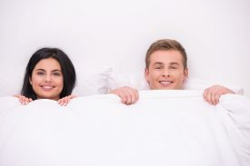 stock photo of early 20s  - Top view photo of smiling young couple lying in white bed early in the morning under white blanket and looking at camera - JPG