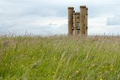 picture of broadway  - Broadway Tower and grass in the Worcestershire part of the Cotswolds Hills. Unique folly small castle like tower with amazing views across english countryside. Second highest point on the Cotswold escarpment