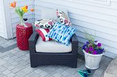 image of spring break  - Pile of colorful cushions on a comfortable outdoor armchair flanked with fresh spring tulips and flowers for a relaxing place to enjoy a shady break on a hot day - JPG