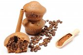 stock photo of cinnamon  - Closeup of fresh baked coffee muffins coffee grains powdery cinnamon on wooden spoon cinnamon stick bitten muffin - JPG