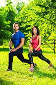 stock photo of stretch  - Man and woman doing stretching exercises at summer park - JPG