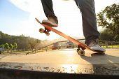 pic of skateboard  - skateboarder legs riding on skateboard at skatepark ramp - JPG