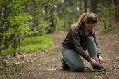 foto of jogger  - Image of female jogger tying sporty shoes - JPG