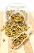 picture of chamomile  - Closeup of dried chamomile dried chamomile pouring out of glass jar and heap of chamomile on wooden spoon - JPG