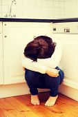 image of lonely woman  - Lonely depressed woman sitting on kitchen floor - JPG