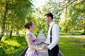 stock photo of suspenders  - Young couple in love holding hands and looking each other in the eyes in summer park  - JPG