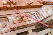 image of bricklayer  - Mason bricklaying background with level hammer and clay brick blocks - JPG