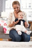 pic of kneeling  - Young mother holding on lap baby daughter - JPG
