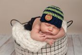 stock photo of beanie hat  - Three week old newborn baby boy wearing jeans and a crocheted blue and green beanie hat - JPG
