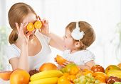 picture of healthy eating girl  - happy family mother and daughter little girl eat healthy vegetarian food lots of fruit - JPG