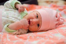 image of papule  - Newborn baby with hormonal rash sucks on fist - JPG