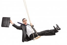 picture of swing  - Studio shot of a delighted young businessman swinging on a swing and holding a suitcase isolated on white background - JPG