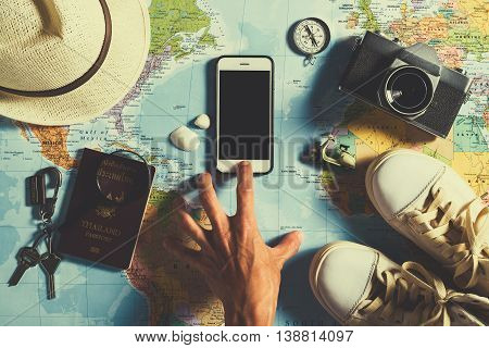 poster of Travel concept The hand of traveler push on a smart phone Traveler accessories with passport shoe camera hat compass keys magnifier and smart phone