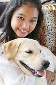 pic of young girls  - Smiling Asian girl on animal print sofa with her pet dog