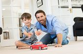 Father with little boy playing with toy car. Smiling father and happy son playing together in living poster
