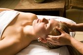 picture of massage therapy  - woman in a day spa getting a head massage by therapist - JPG