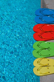 stock photo of swimming pool family  - Colored flipflops of a family of four by the swimming pool - JPG