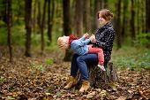 Little Boy With His Young Mother Having Fun During Stroll In The Forest. Active Family Time On Natur poster