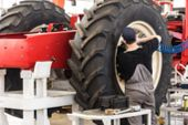 Worker Assembles Tractor Or Combine Harvester At Large Machinery Plant. Industrial Concept Of Heavy  poster