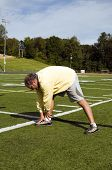 picture of hamstring  - handsome middle age senior man stretching legs hamstrings exercising on sports field touching toes - JPG