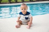 Cute baby boy sitting dangerously on the edge of a swimming. Concept photo of swimming pool danger a poster