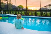 Rear view of a child sitting on the edge of a backyard swimming pool. Concept photo of swimming pool poster