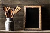 Wooden Kitchen Cooking Tools With Spoons And Spatula In Metal Can In Front Of Rustic Wooden Board Ba poster