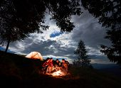 Night Camping In The Mountains. Group Of Friends Hikers Having A Rest Around Campfire With Beer, Enj poster