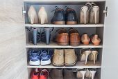 Close Up Fashionable Women High Heels, Leather Men Shoes And Sport Shoes In Wooden Cabinet For Going poster