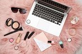 Flat Lay Composition With Laptop, Notebook And Makeup Products For Woman On Fur poster