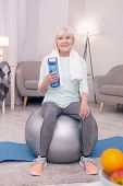 Vital Hydration. Cheerful Elderly Woman Sitting On The Balance Ball And Posing With A Bottle Of Wate poster