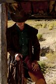 stock photo of cowboy  - A cowboy is standing by a cabin post with a bridle in his hand - JPG