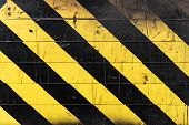 Texture Of Black And Yellow Stripes On The Wall. Hazard Or Danger Grungy Background. poster
