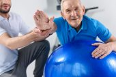 Partial View Of Rehabilitation Therapist Assisting Smiling Senior Man Exercising On Fitness Ball poster