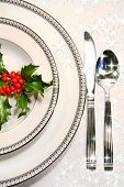 stock photo of christmas dinner  - Silver plate setting with a sprig of holly and stars - JPG