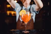 Close-up Of Barman Mixes Cocktail With Ice Orange, Whiskey, Liquor. poster