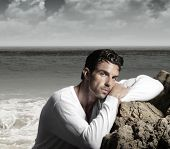 Fashion portrait of a handsome man in exotic  beautiful beach landscape