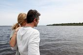 stock photo of stressless  - Profile view of couple sitting on a wooden bridge by a lake - JPG