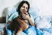 Smiling Woman Waking Up After Sleep On Bed With Red Fatty Cat. Brunette Hugs And Strokes Her Cat. Wa poster