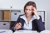 Business woman sitting with headache at her desk in the office