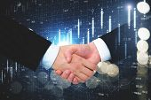 Businessmen Handshake On Blurry  Forex Chart Grid. Teamwork And Finance Concept. Double Exposure poster