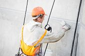 stock photo of mortar-joint  - Facade plasterer at outdoor wall renovation making off joints - JPG
