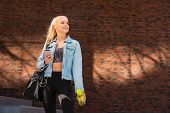 Attractive woman in sportswear walking to a gym outdoor. Sport, jogging, healthy and active lifestyl poster