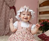 little child baby girl sitting indoors babyroom dress hat smiling happy