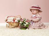stock photo of cute little girl  - little child baby girl  indoors in baby room playing on the floor with flowers - JPG