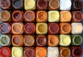 stock photo of marinade  - 35 small colored bottles with various sauces - JPG