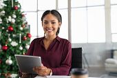 Happy business woman using digital tablet in modern office with christmas tree in background. Portra poster