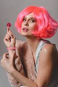 Young Attractive Woman In A Bright Pink Wig, Golf And Faux Fur Coat. poster