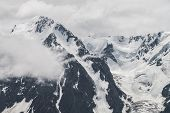 Atmospheric Minimalist Alpine Landscape Of Big Snowy Mountain With Massive Glacier. Low Cloud Among  poster